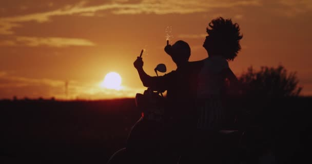 Amazing sunset beautiful couple stand behind the retro motorcycle happy holding sparklers looking to amazing nature view. slow motions. silhouette
