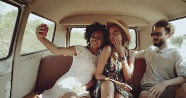 Charismatic girls african and blonde with a beautiful white smile with a guy who wearing a glasses going on the way in a vintage retro bus taking selfie from the phone