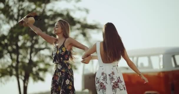 Pretty young ladies with long hair dancing happy in the middle of nature wearing a stylish retro dress.