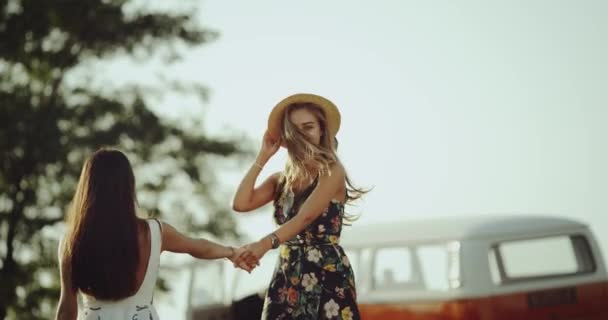 Very photogenic young female spending a good time together , in the middle of nature smiling and happy hugging each other , wearing retro hat and dresses.