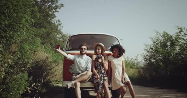 Three friends , having a nice time together wearing retro stylish clothes, beside the orange vintage bus beside the road , taking selfie using a phone.
