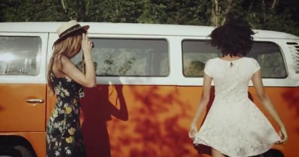 Dva přátelé mladé ženy, africké a blondýna, pořizování snímků s použitím ročník fotografické kamery charismatický úsměv a nosit retro šaty