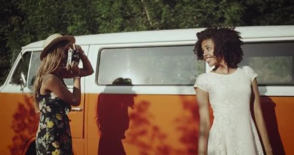 Vedle vinobraní oranžový autobus dva charismatický dívky Africké a blond jeden pořizování snímků z fotoaparátu vinobraní fotografie s úsměvem a s šťastné tváře