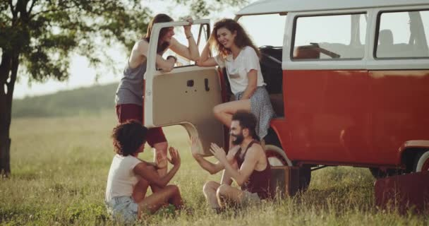 Group of friends have a good time together in the middle of nature playing with hands , standing up beside of a retro bus.