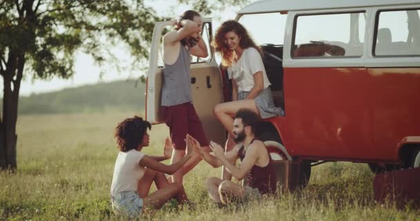 Two couples going out at nature with their retro bus , and standing beside of a big tree , spending a good time together speaking and playing games.