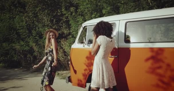 Two pretty girls making photo shoot on the road beside the vintage orange bus , happy dancing and smiling , wearing boho style clothes.