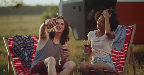 African curly hair ladie with her long hair friend man taking pictures at the picnic in a beautiful place beside of their retro van , drinking wine , sitting on chairs. 4k