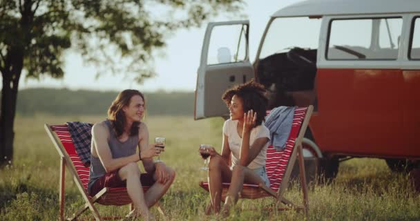 Nice conversation with a glass of wine in the middle of nature, two friends  african woman and young man , sitting on chairs and have a good time