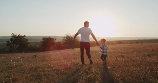 Běží mladý táta se synem tří let při západu slunce, úžasný výhled na.