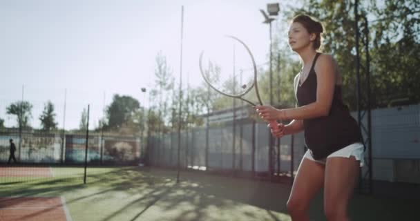 Good looking professional female tennis player, playing tennis outside at tennis court.