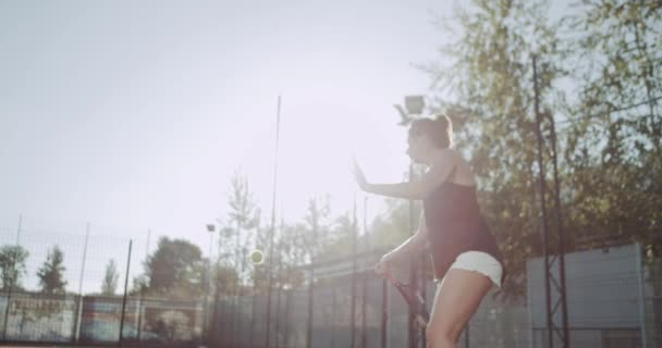 Young female playing tennis outdoor on tennis court. 4k