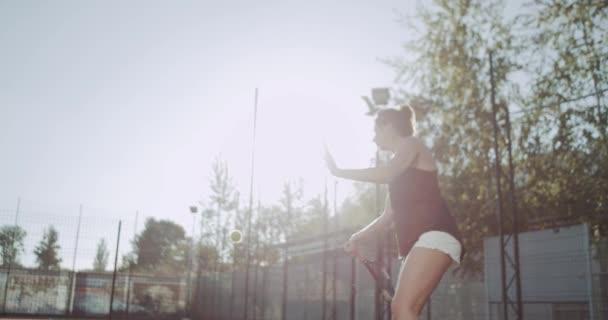 Mladá žena hrát tenis venkovní na tenisový kurt. 4k