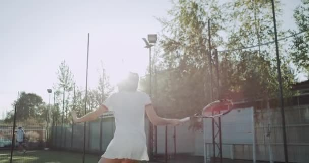 Outdoor tennis court , one professional player female playing with her partner professional equipped, nice sunny day. 4k