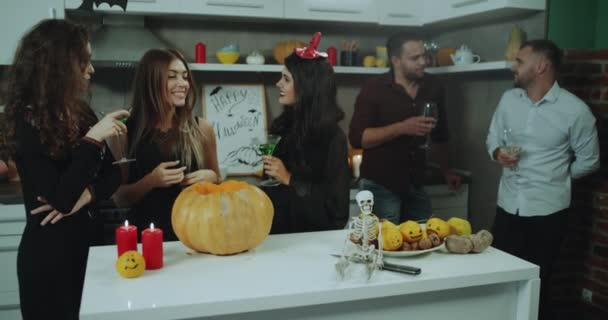 Big Halloween party at home , guest in the kitchen masked for Halloween drinking cocktails and wine, amazing Halloween atmosphere. 4k