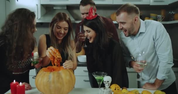 Home party on Halloween night, guest trying to take something out from a big pumpkin , they holding glass of cocktail and wine , have a charismatic faces. 4k