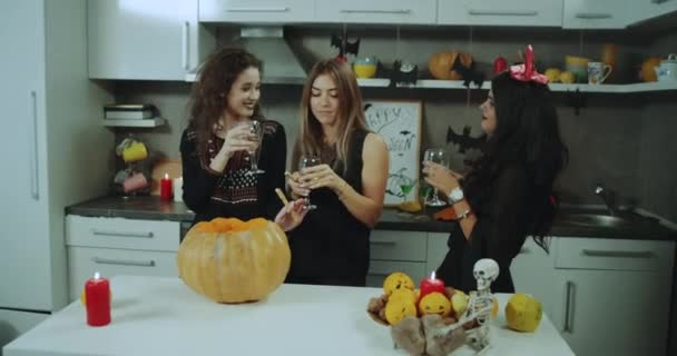 At Halloween night young ladies dancing happy and holding glasses of wine , spending a great time together.
