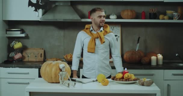 Funny time in the kitchen a man prepare the decoration for Halloween party, he starting to playing with some oranges juggling, dacing and smiling in front of the camera.