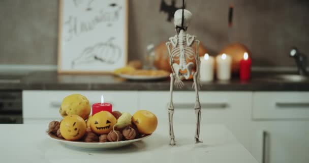 Halloween decorations on the kitchen, candles ,pumpkins , a very funny dacing a skeleton on the kitchen table.