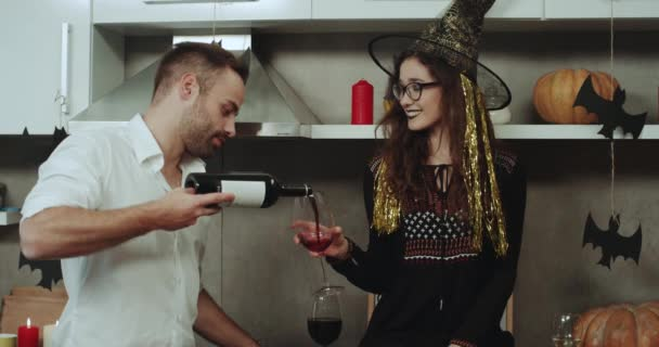 Charismatic couple with large smile at Halloween party , the man holding a bottle of red wine and and pour a bit on the glasses , amazing Halloween atmosphere with candles and pumpkins.