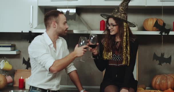 A Halloween mood for one couple , lady masked in a witch and drinking wine with her partner, on the kitchen amazing decorations with candles and pumpkins.