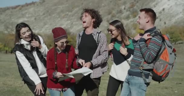 A company with girls and boy have a trip time , in the middle of mountain using a map to find the right destination for exhibition , smiling faces.