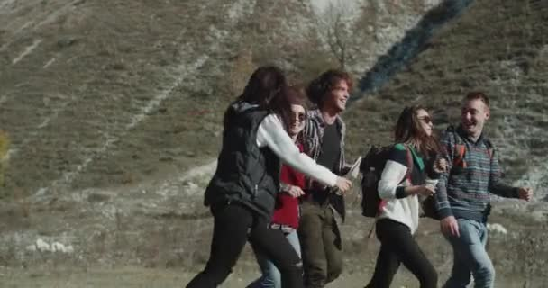 Good time for five friends , in the mountain trip , walking through the field happy and smiling holding in their back a big trip bags.