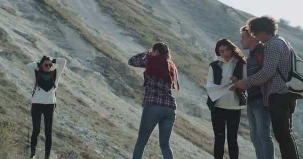 Group of multicultural friends have a trip in the middle of mountain, two girls making pictures for memories, other fiends trying to find the short way using a map. 4k