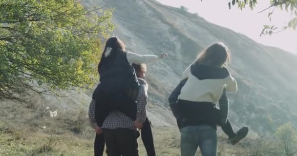 Two couple have a fun time together in the middle of mountain, girls are jumping over the their boyfriends back and happy spending a perfect time together.