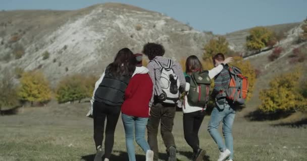 Group of friends on the mountain trip with bags walking through the field hugging each other. shot on red epic