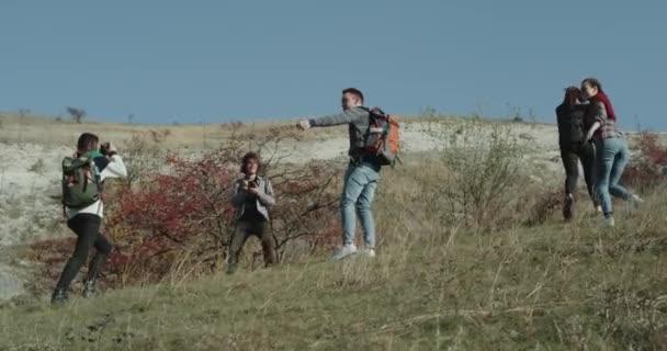 Bilder-Zeit für Gruppe von Freunden, die in einer Ausstellung sie zu Fuß auf Berg sind, gehen hart, haben im Rücken eine große Reise-Taschen