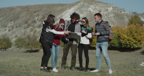 Multicultural group of friends have a exhibition in the middle of mountain, they get lost and using a map trying to find the right way.
