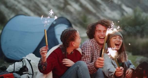 Vértes mosolygó nagy meg van egy nagy buli a hegyi camping, gazdaság néhány csillogó tűzijáték és ünnepli valami a tábortűz