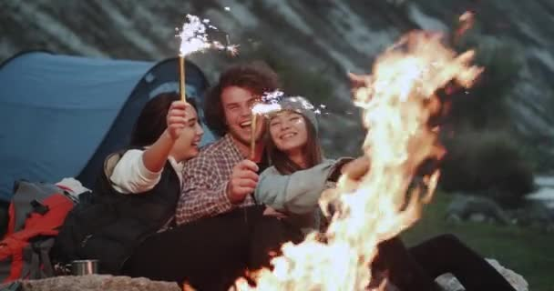 Amazing capturing of friends that holding sparkling fireworks at campfire, celebrating something.