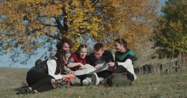 Posto incredibile a natura, un gruppo di amici seduti sullerba e guardando attraverso una grande mappa, cercando di trovare una prossima destinazione volti felici e sorridenti, trascorrere un buon tempo insieme.