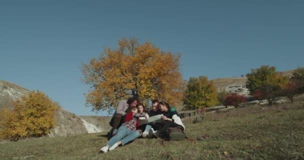 Bellissimo posto in natura al lato di un giovane di grande albero variopinto multicultural persone hanno un tempo di pausa della loro esposizione, usando una mappa per trovare un modo breve per la montagna, che siede sulla