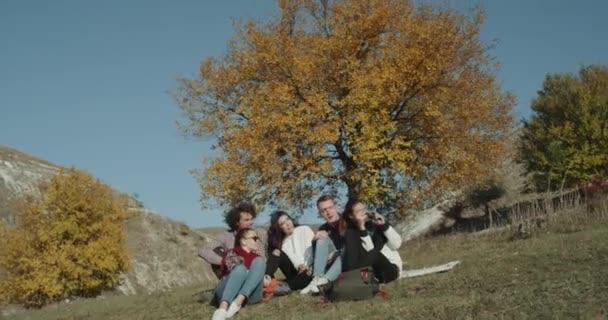 Gli amici multiculturali hanno una bellissima Mostra sulla natura, scattare foto fino a hanno una pausa sotto un grande albero colorato.