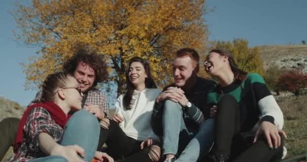 Gruppo di amici durante il viaggio sorridente hanno un momento di pausa, raccontando storie divertenti.