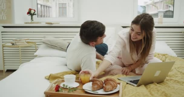 Beautiful couple in the morning taking breakfast in bed and have a look through a notebook they smiling and happy spending amazing time.