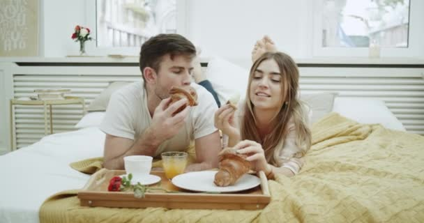 In the morning a cute couple have breakfast in bed eating French croissants and have a conversation , very cozy atmosphere.