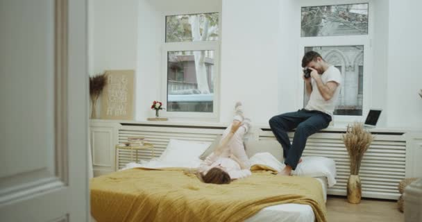 Amazing cozy design in bedroom , one couple have a romantic time together , man make some pictures for the lady they are both in pajamas.