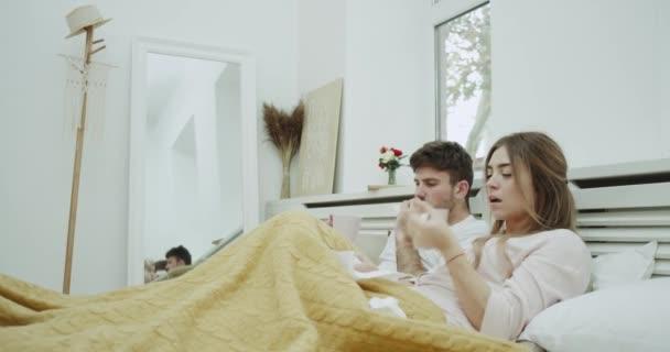 laufende Nase für ein junges Paar, das sehr krank ist und Tee unter einer warmen Decke auf dem Bett trinkt