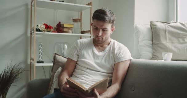 V obýváku muž sedí na pohovce a čtení, kniha, moderní design a okolí