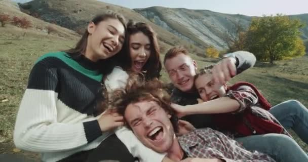 In the middle of nature group of young ladies and guy making selfie video with camera , smiling large , multicultural people.