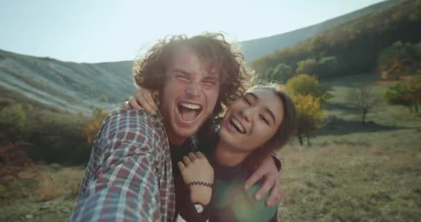 Pretty Asian lady And her boyfriend have a trip together in the middle of amazing landscape they taking video for memories filming their self and happy hugging each other and smiling large in front of