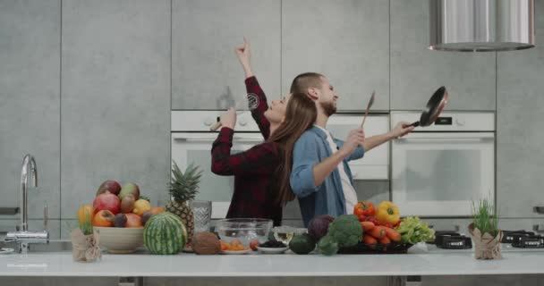 Charismatic funny couple in the morning dacing and singing in the kitchen using a pan and a hand mixer they have a crazy morning before making a healthy breakfast , a kitchen island are full of fruits