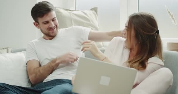 Happy couple spending a lovely time together hugging and playing with each other and watching something on the notebook they are sitting on the sofa in cozy living room
