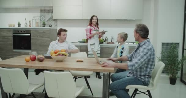 Big family in the morning have a healthy colorful breakfast beautiful mature mom preparing food for her boys and putting on the dinner table dad happy sitting beside and working on his laptop , mature