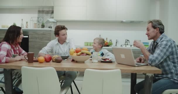 Charismatic mature family eating healthy food, they have a breakfast sitting at the dinner table happy spending a time together , in a modern kitchen , father working on the laptop while drinking his