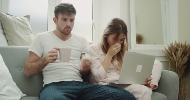 Hustenendes Paar am Morgen hat Grippe und laufende Nase Mann trinkt etwas Warmes aus einer Tasse und Frau checkt ihr Notizbuch E-Mail.