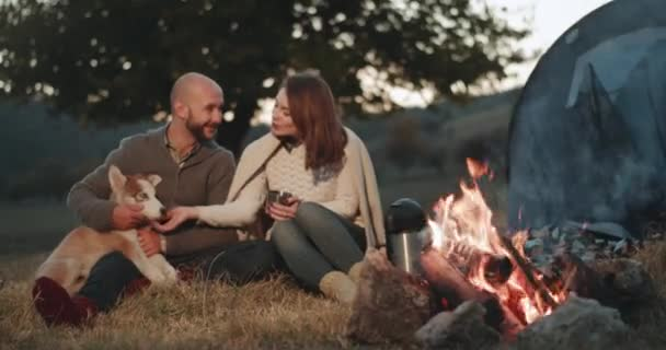 Picnic time for our young couple in the middle of nature beside of campfire spending a lovely time together with their husky dog hugging each other. 4k